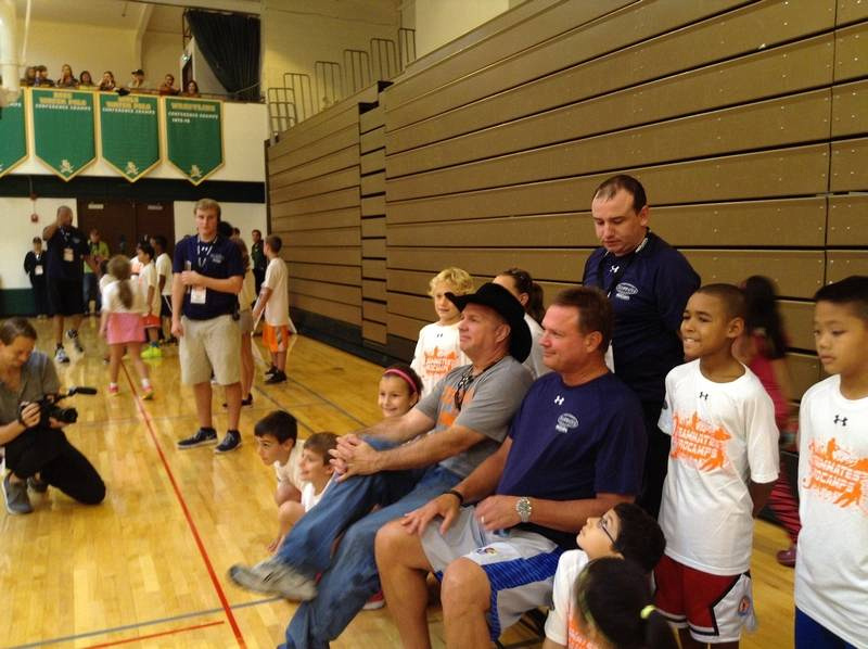 Buddies from their college days together, country music superstar Garth Brooks, in his trademark black hat, and University of Kansas head basketball coach Bill Self sit for a photo with kids at the ProCamp basketball camp Saturday at Elk Grove High School. The event was sponsored by Brooks